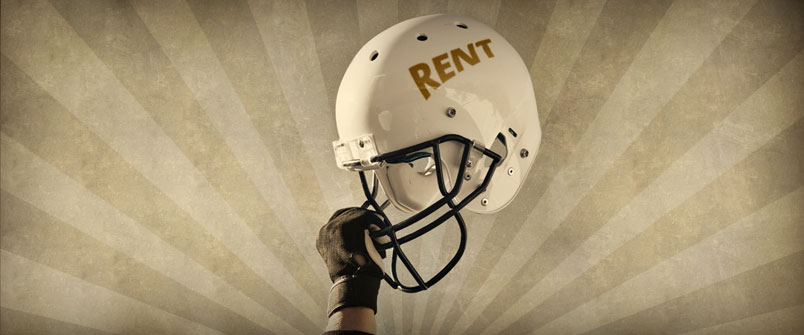 "Person holding a football helmet with ""Rent"" on the side"