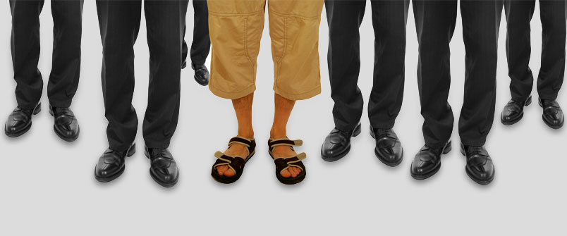 The legs of a bunch of well dressed people, and one person wearing capris and sandals