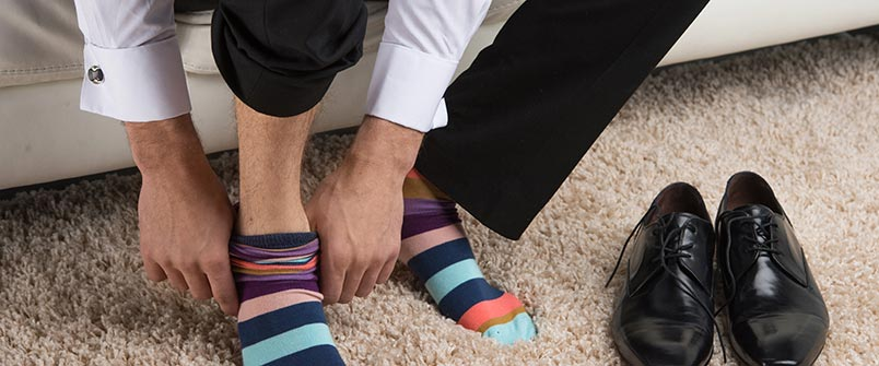 Guy putting on dress socks