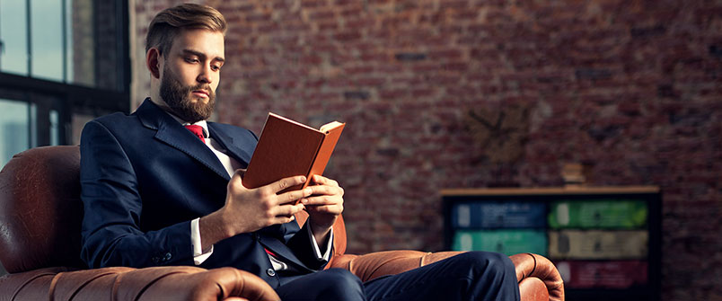 Well dressed man reading a book
