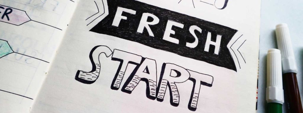 The words 'fresh start' drawn in a notebook